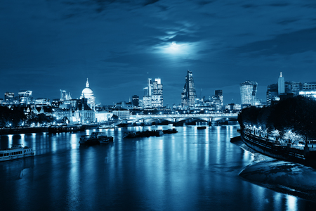 cityscape: London cityscape with urban buildings and moon over Thames River at night Stock Photo