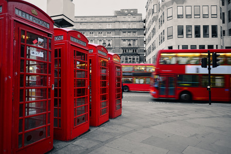 historical architecture: Red telephone box and bus in street with historical architecture in London. Stock Photo