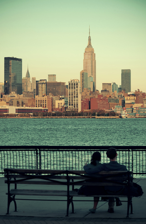 couple in love: Couple de repos sur le banc à regarder New York gratte-ciel Banque d'images