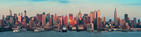 sunset city: New York City skyscrapers urban view at sunset and moon rise.