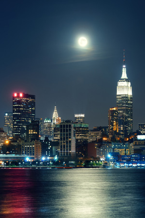 city skyline: Moon rise over midtown Manhattan with city skyline at night Stock Photo
