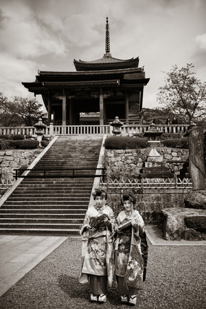 former years: KYOTO, JAPAN - MAY 18: Geisha stand in Shrine on May 18, 2013 in Kyoto. Former imperial capital of Japan for more than one thousand years, it has the name of City of Ten Thousand Shrines.