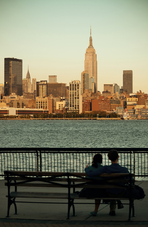 ny: Couple rest on bench watching New York City skyscrapers