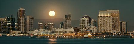 anochecer: San Diego horizonte de la ciudad y la luna llena sobre el agua en la noche