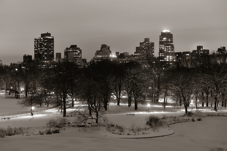 white winter: Central Park winter at night with skyscrapers in midtown Manhattan New York City Stock Photo