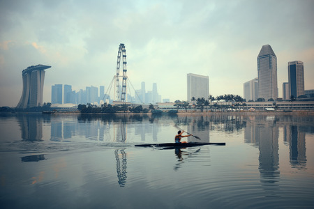 bateau: Singapore skyline avec des bâtiments urbains et bateau réflexion sur l'eau Éditoriale