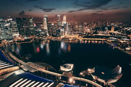 밤에 도시의 마천루와 싱가포르 마리나 베이 (Marina Bay)의 옥상 전망입니다.