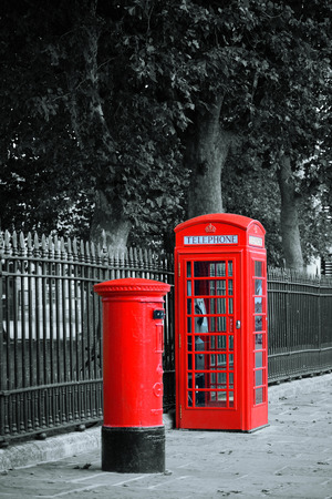 red box: Red telephone and post box in street with historical architecture in London.