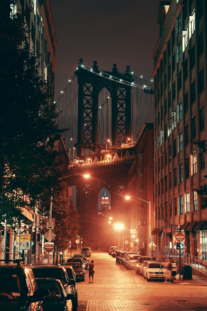 Manhattan Bridge viewed from street at night Редакционное
