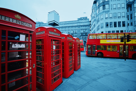 telephone box: Red telephone box and bus in street with historical architecture in London. Editorial