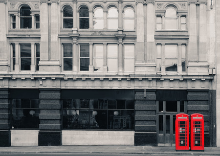 telephone booth: Red telephone booth in street with historical architecture in London.