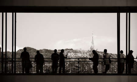 evolved: Los Angeles, CA - MAY 18: Tourists and Hollywood sign on May 18, 2014 in Los Angeles. Started as a small community, it evolved into the home of world famous film industry
