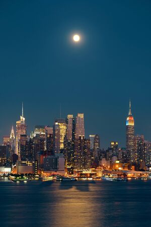 nighttime: Moon rise over midtown Manhattan with city skyline at night Stock Photo