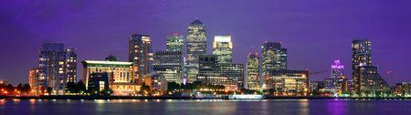 Canary Wharf business district in London at night over Thames River.