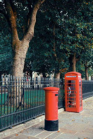 red post box: Red telephone and post box in street with historical architecture in London.