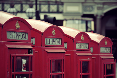 red telephone: Red telephone box in street with historical architecture in London. Stock Photo