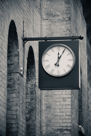 old street: Urban historical architecture with vintage clock in street in London. Stock Photo