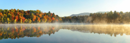 Lake fog panorama with Autumn foliage and mountains with reflection in New England Stowe 免版税图像