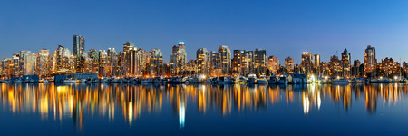 Vancouver downtown architecture and boat with water reflections at dusk panorama 版權商用圖片