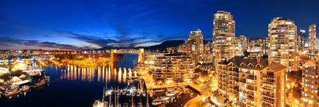 metropolis: Vancouver harbor view with urban apartment buildings and bay boat at dusk in Canada.