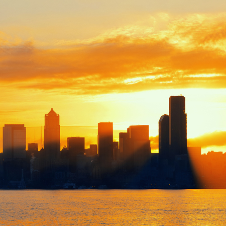 sunshine state: Seattle sunrise skyline silhouette view with urban office buildings. Stock Photo