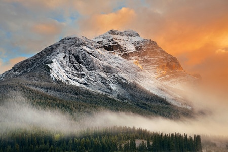 Snow capped mountain and fog at sunset in Yoho National Park in Canada 스톡 콘텐츠