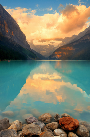 Lake Louise at sunrise with rocks in Banff national park with mountains and forest in Canada. Stock Photo