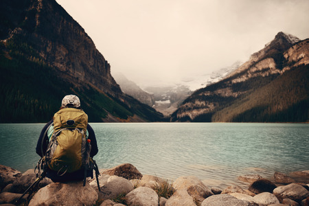 A female hiker at Lake Louise in Banff national park with mountains and forest in Canada.