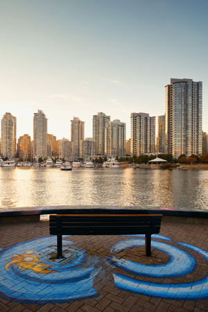 waterfront: A bench at Vancouver waterfront with apartment buildings.