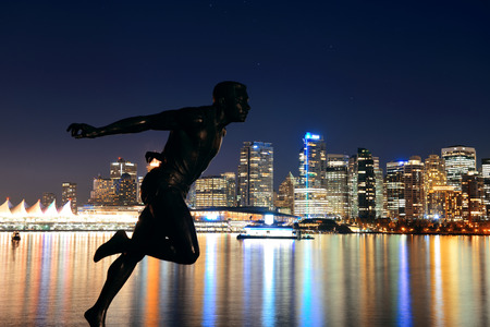 bc: Vancouver city architecture at night and statue of Harry Jerome in Canada
