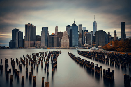 pier: Manhattan financial district with skyscrapers and abandoned pier over East River.