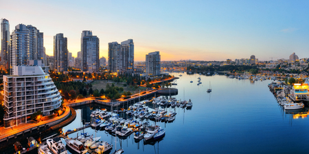 Vancouver harbor view with urban apartment buildings and bay boat in Canada. 版權商用圖片