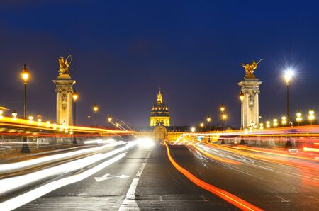 Alexandre III bridge night view with Napoleons tomb and light trail in Paris, France. Stock Photo