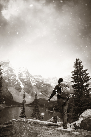 snow capped mountain: Hiker in Moraine Lake with snow capped mountain of Banff National Park in Canada in a snowing day