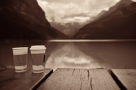 louise: Lake Louise with coffee cup at sunrise in Banff national park with mountains and forest in Canada.