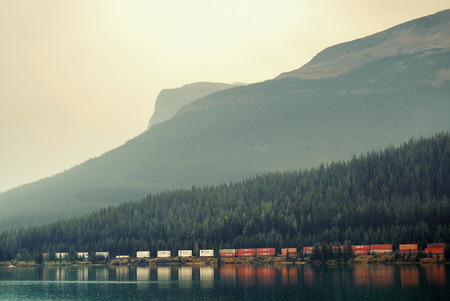 railway transportations: BANFF, CANADA - AUGUST 27: Cargo train lake and mountain on August 27, 2015 in Banff National Park, Canada. Established in 1885, it is the oldest park in Canada.