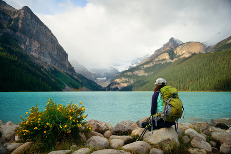 louise: A female hiker at Lake Louise in Banff national park with mountains and forest in Canada.