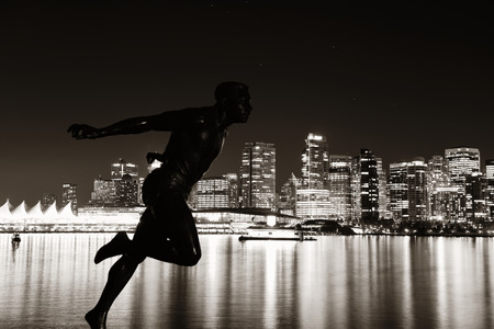 city at night: Vancouver city architecture at night and statue of Harry Jerome in Canada
