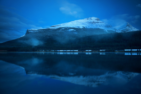 snow capped mountain: Snow capped mountain with lake reflection in a foggy dusk in Banff National Park, Canada.