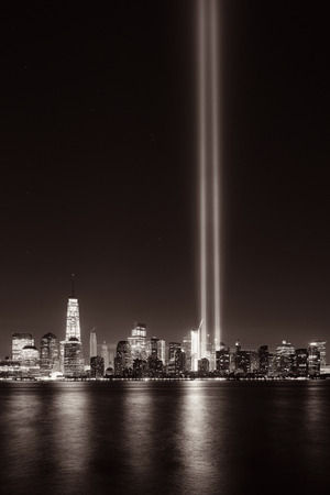 tribute: New York City downtown urban architecture at night and September 11 tribute light