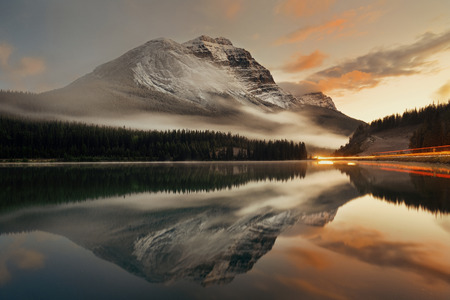 light trail: Mountain lake and traffic light trail with reflection and fog at sunset in Banff National Park, Canada.
