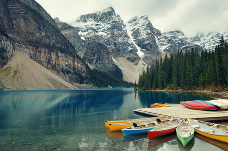 banff national park: Moraine Lake and boat with snow capped mountain of Banff National Park in Canada Stock Photo