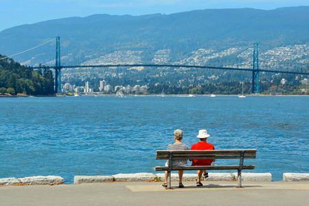 An old couple sit at waterfront in Vancouver with Lions Gate Bridge over sea
