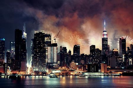 fuegos artificiales: Espectáculo de fuegos artificiales con los rascacielos de Manhattan midtown y el horizonte de la ciudad de Nueva York en la noche