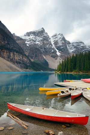 snow capped mountain: Moraine Lake and boat with snow capped mountain of Banff National Park in Canada Stock Photo