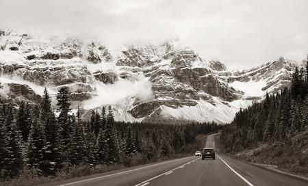 snow capped mountain: Highway with snow capped mountain forest and car in Banff National Park, Canada Stock Photo