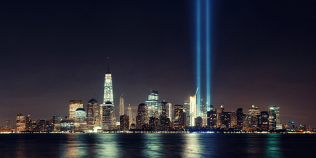 tribute: New York City downtown skyline at night panorama over Hudson River and September 11 tribute light Stock Photo