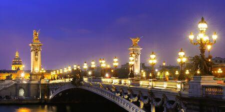 paris night: Alexandre III bridge night view panorama with Napoleons tomb in Paris, France.