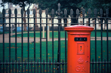 red post box: Red post box in street with historical architecture in London.