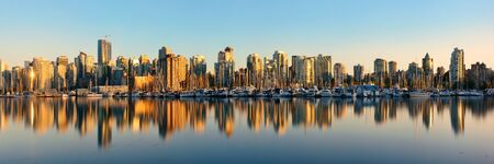 british columbia: Vancouver downtown architecture and boat with water reflections at sunset panorama